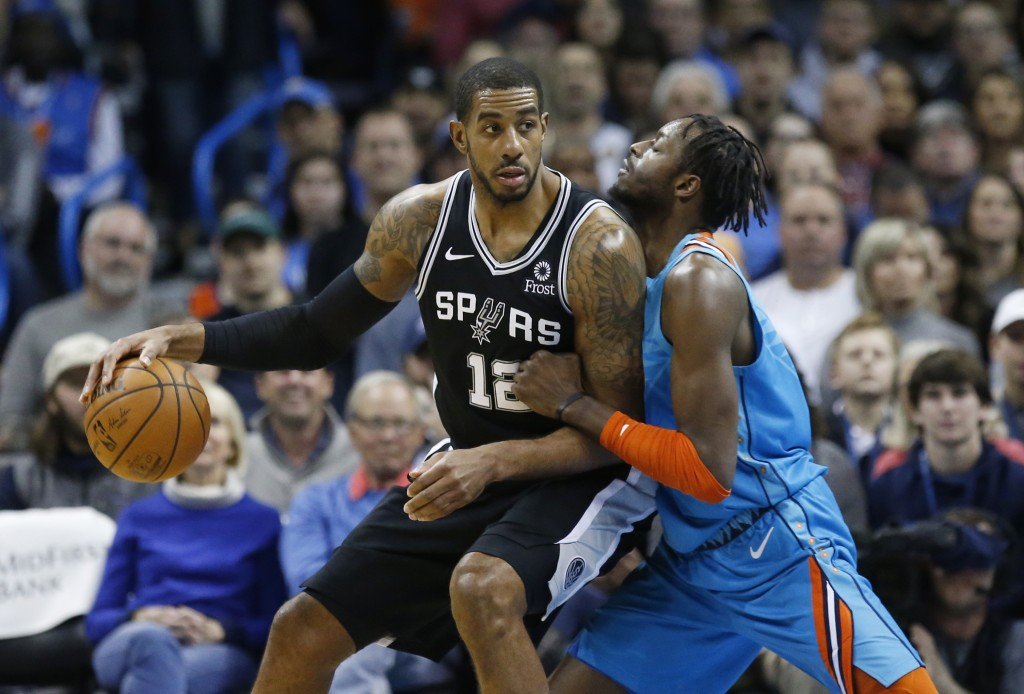 San Antonio Spurs forward LaMarcus Aldridge (12) drives against Oklahoma City Thunder forward Jerami Grant, right, in the first half of an NBA basketb