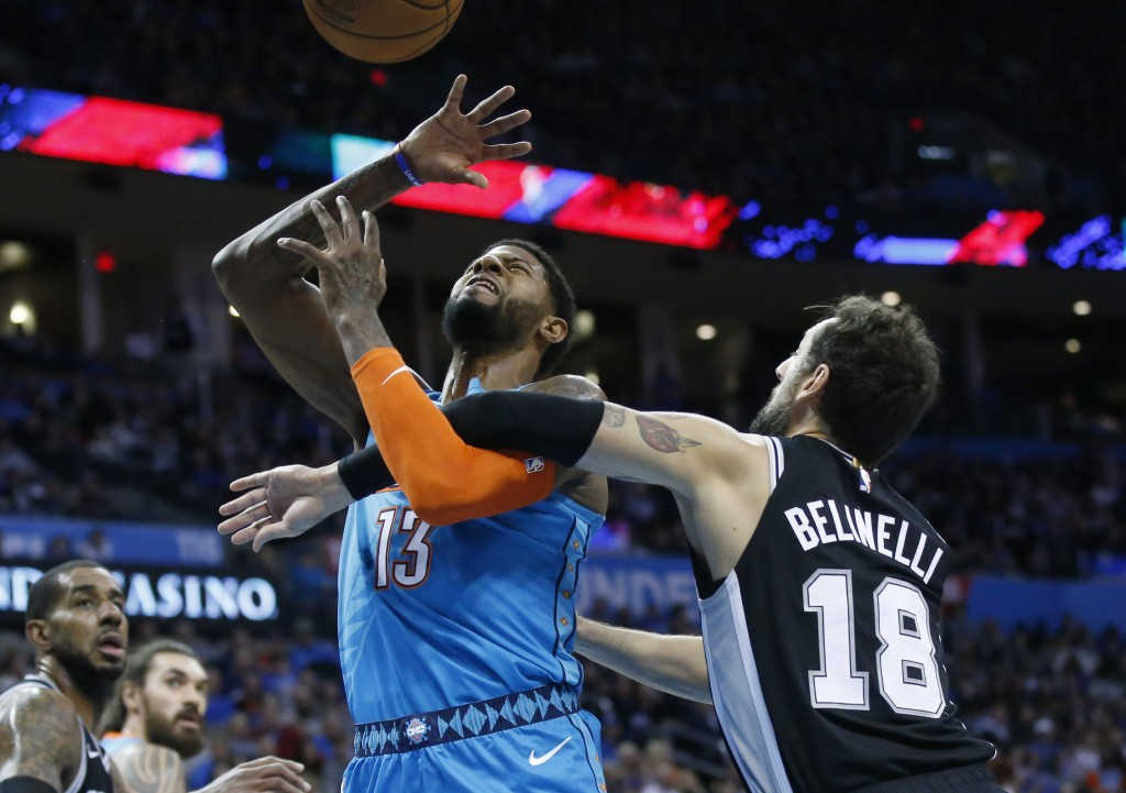 Oklahoma City Thunder forward Paul George (13) loses the ball as he is fouled by San Antonio Spurs guard Marco Belinelli (18) in the first half of an