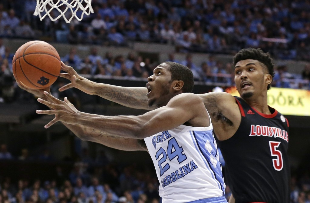 North Carolina's Kenny Williams (24) drives to the basket while Louisville's Malik Williams (5) defends during the first half of an NCAA college baske