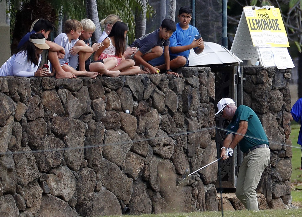 Children watch along the wall as Stewart Cink hits from a backyard along the first fairway during the third round of the Sony Open golf tournament Sat...