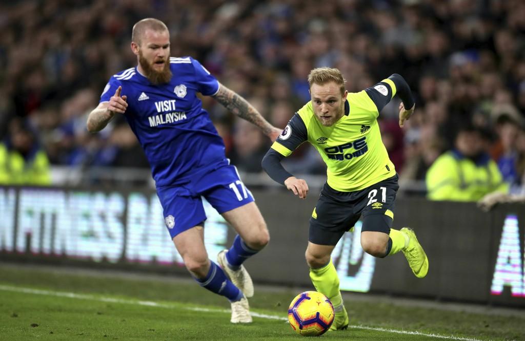 Cardiff City's Aron Gunnarsson, left, and Huddersfield Town's Alex Pritchard chase the ball during the English Premier League soccer match between Car