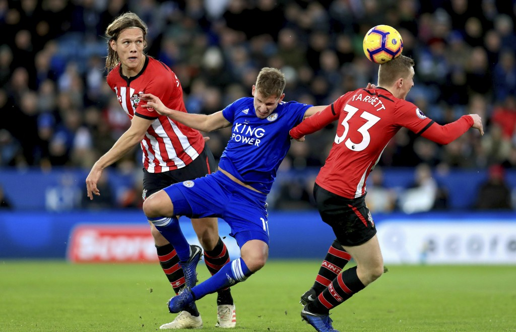 Leicester City's Marc Albrighton, center, battles for the ball with Southampton's Matt Targett, right, and Jannik Vestergaard during the English Premi
