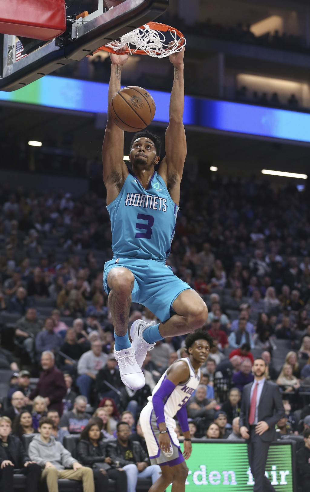 Charlotte Hornets guard Jeremy Lamb hangs from the rim after a dunk as Sacramento Kings guard De'Aaron Fox, rear, watches during the first quarter of