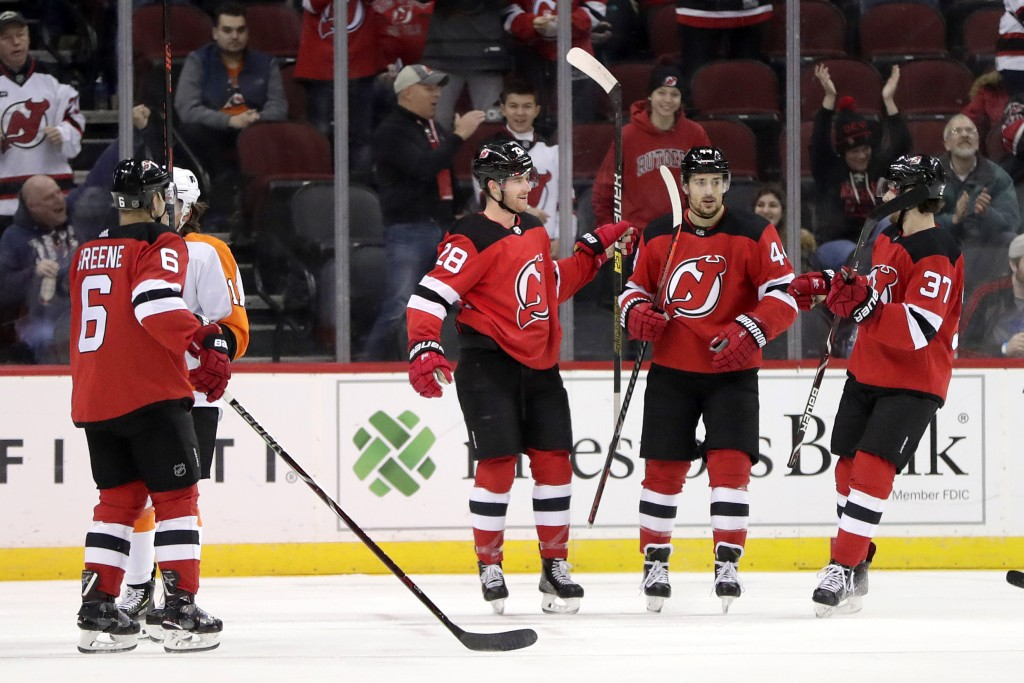 New Jersey Devils defenseman Damon Severson, second from left, celebrates his first period with teammates during an NHL hockey game against the Philad