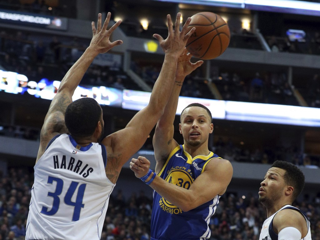Golden State Warriors guard Stephen Curry (30) passes the ball around Dallas Mavericks guard Devin Harris (34) in the first half of an NBA basketball