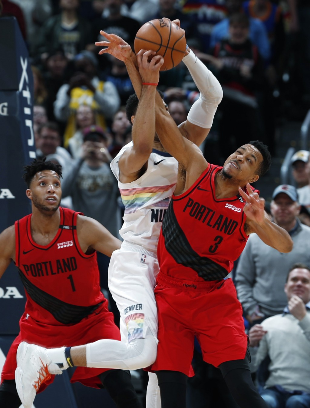 Portland Trail Blazers guard CJ McCollum, right fouls Denver Nuggets guard Jamal Murray as he collects his rebound late in the second half of an NBA b