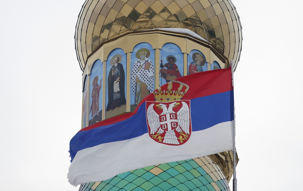 In this photo taken Friday, Jan. 11, 2019, the Serbian flag flies near a new church under construction designed in the Russian style in the village Ba