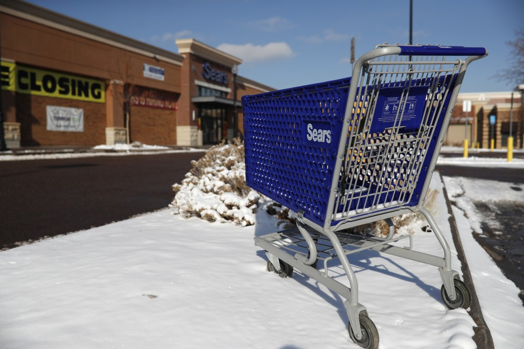 FILE- In this Tuesday, Jan. 1, 2019, file photo, an empty shopping cart sits outside a Sears store in the Streets of Southglenn mall in Littleton, Col