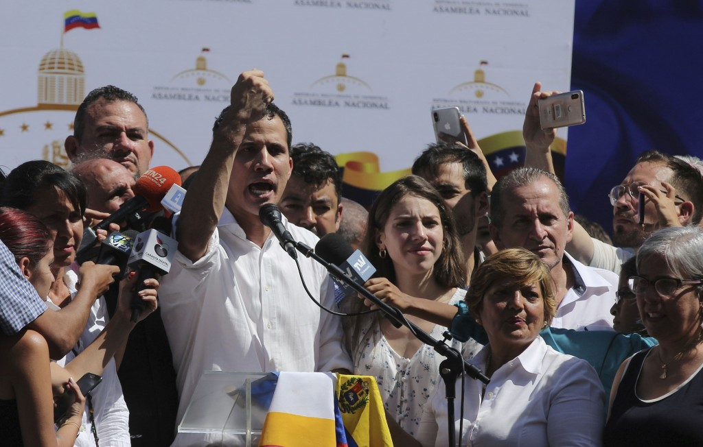Juan Guaido, president of National Assembly, shows marks on his wrists, which he says are from handcuffs, to supporters at a rally in Caraballeda, Ven...