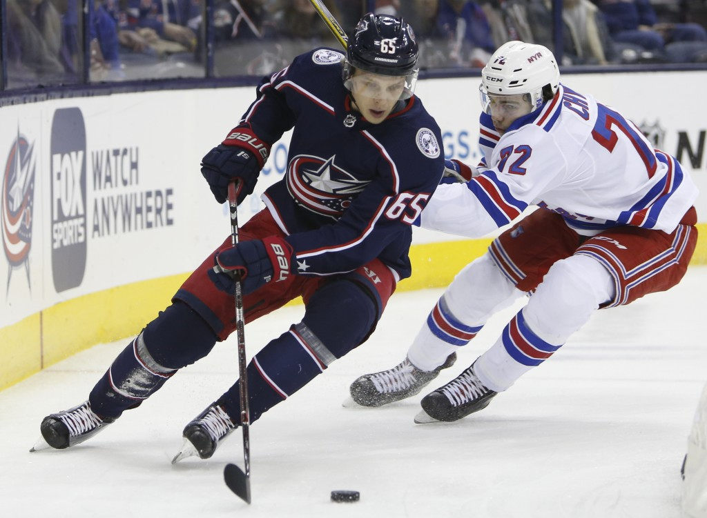 Columbus Blue Jackets' Markus Nutivaara, left, of Finland, tries to clear the puck as New York Rangers' Filip Chytil, of the Czech Republic, defends d