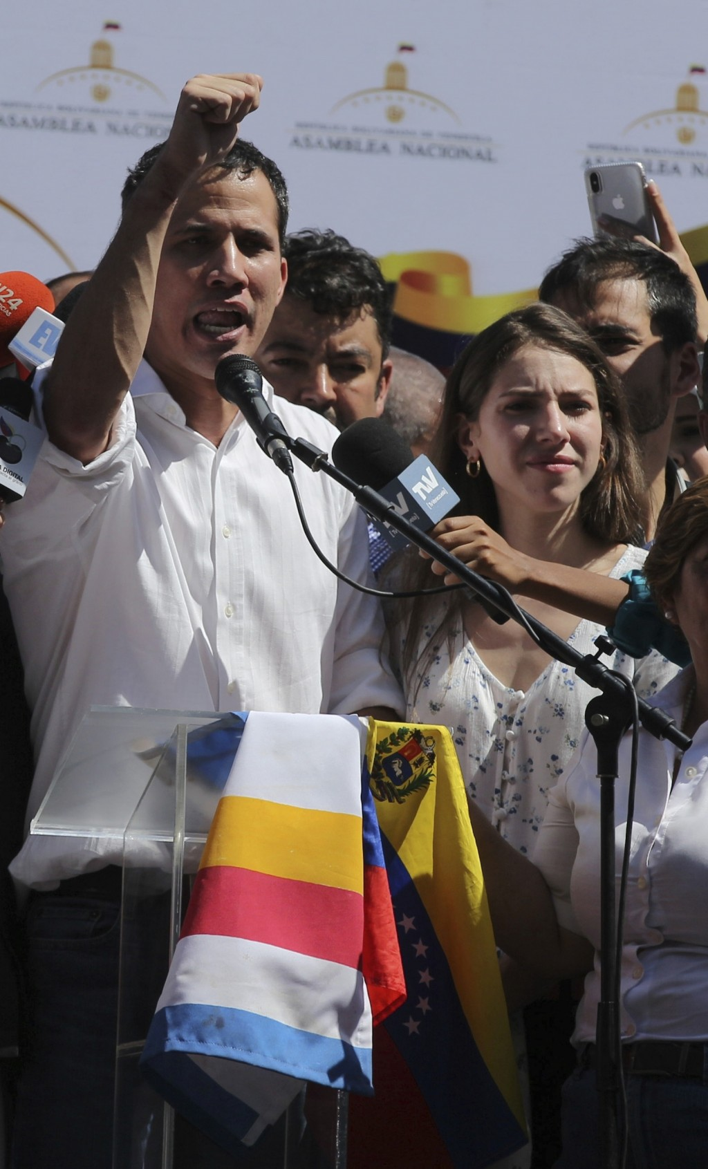 Juan Guaido, president of National Assembly, shows marks on his wrists which he says are from handcuffs, to supporters at a rally in Caraballeda, Vene...