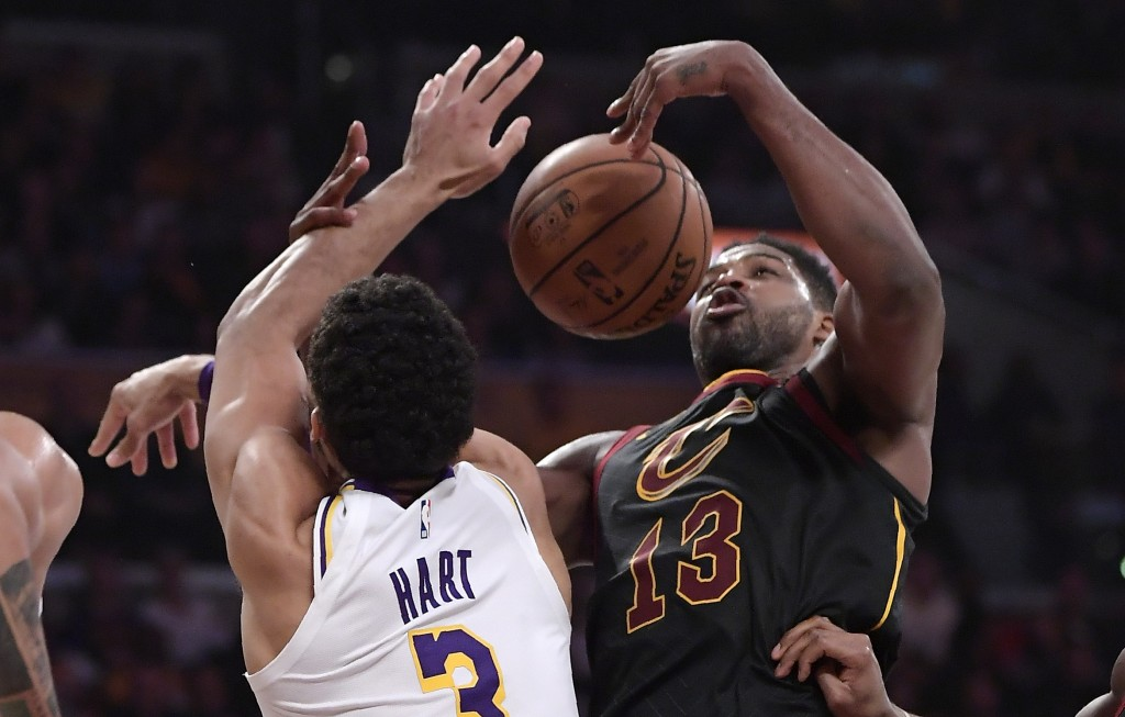Los Angeles Lakers guard Josh Hart, left, and Cleveland Cavaliers center Tristan Thompson grapple for a rebound during the first half of an NBA basket