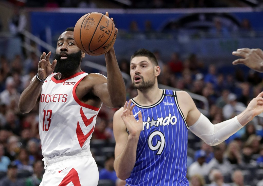 Houston Rockets' James Harden (13) passes the ball away from Orlando Magic's Nikola Vucevic (9) during the first half of an NBA basketball game, Sunda