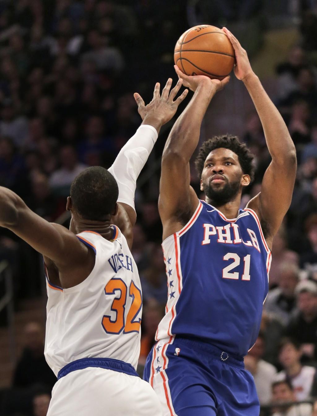 Philadelphia 76ers' Joel Embiid, right, shoots over New York Knicks' Noah Vonleh during the first half of an NBA basketball game, Sunday, Jan. 13, 201