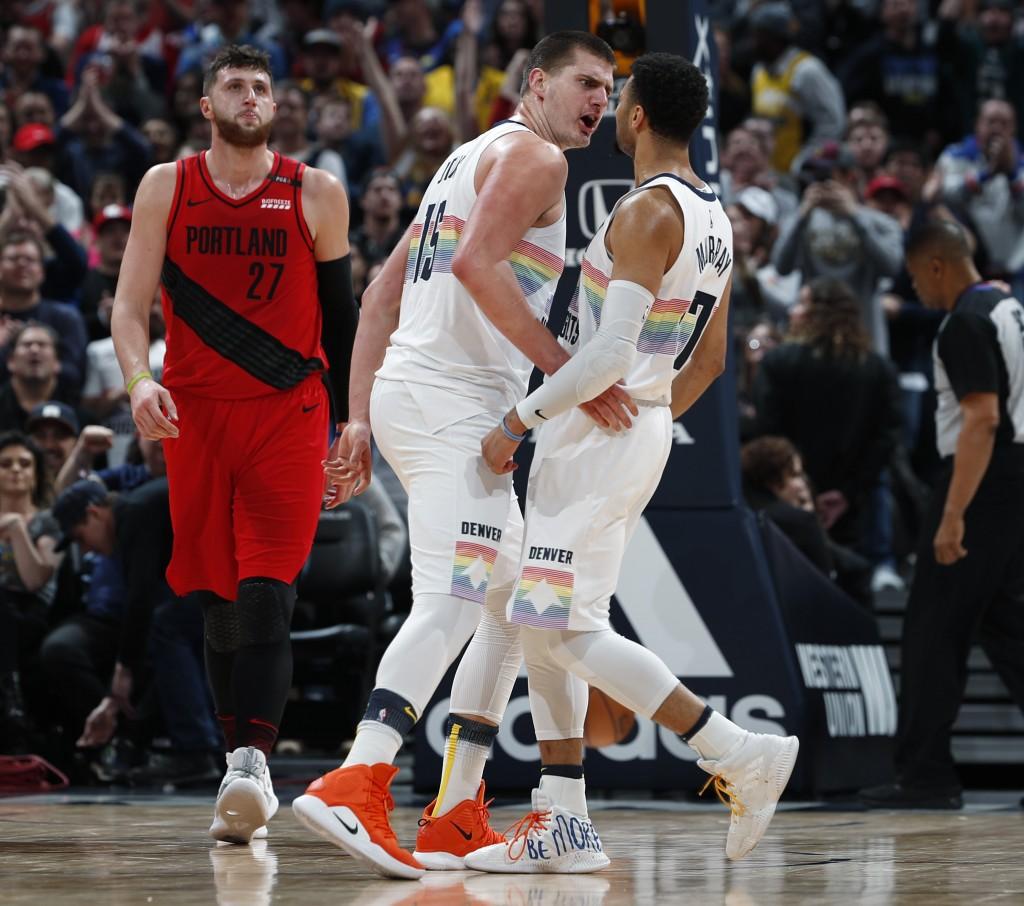 Denver Nuggets center Nikola Jokic, center, celebrates after scoring a basket with guard Jamal Murray, right, as Portland Trail Blazers center Jusuf N