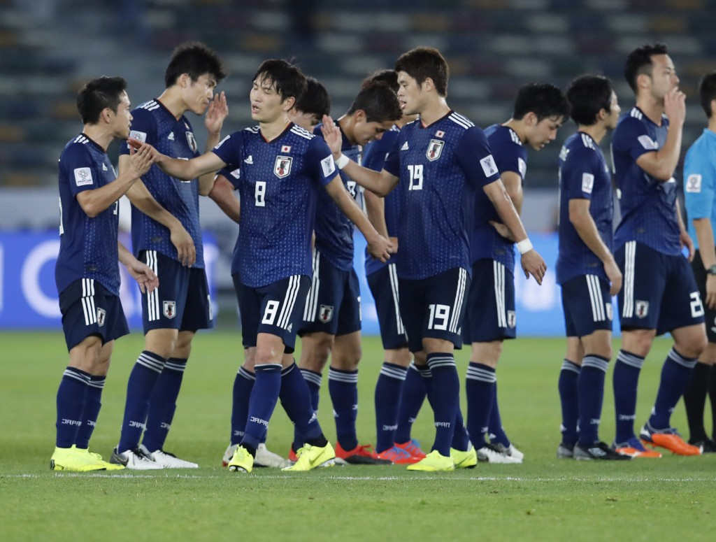 Japan players celebrate at the end of the AFC Asian Cup group F soccer match between Japan and Oman at Zayed Sports City Stadium in Abu Dhabi, United