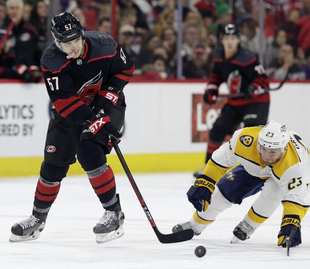 Carolina Hurricanes' Trevor van Riemsdyk (57) and Nashville Predators' Rocco Grimaldi (23) chase the puck during the second period of an NHL hockey ga