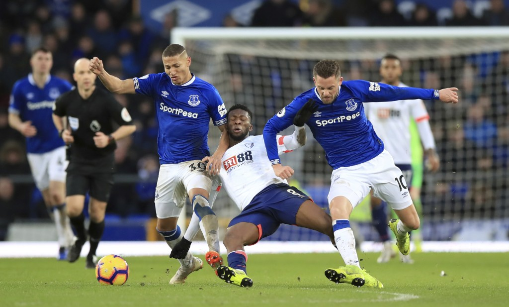 Bournemouth's Jefferson Lerma, center, battles for the ball with Everton's Richarlison, left, and Gylfi Sigurdsson during their English Premier League
