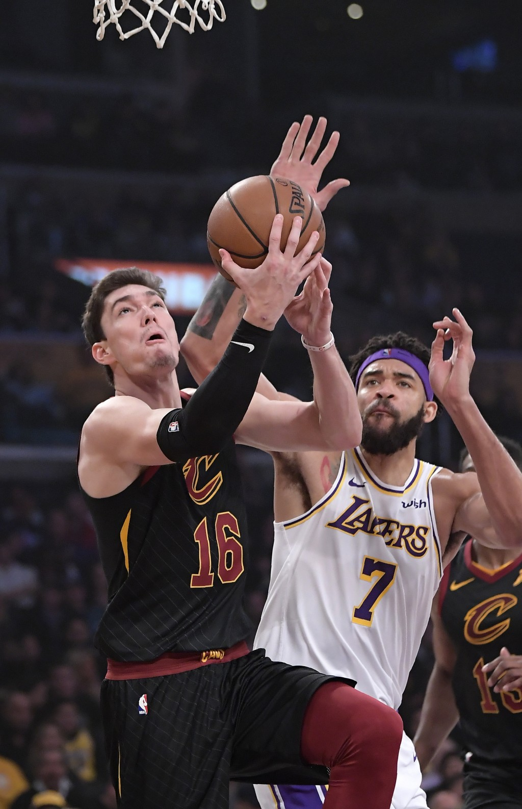 Cleveland Cavaliers forward Cedi Osman, left, shoots as Los Angeles Lakers center JaVale McGee defends during the first half of an NBA basketball game