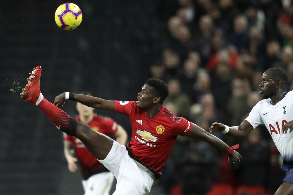 Manchester United's Paul Pogba plays a high ball as Tottenham's Moussa Sissoko, right, runs to block the pass during the English Premier League soccer
