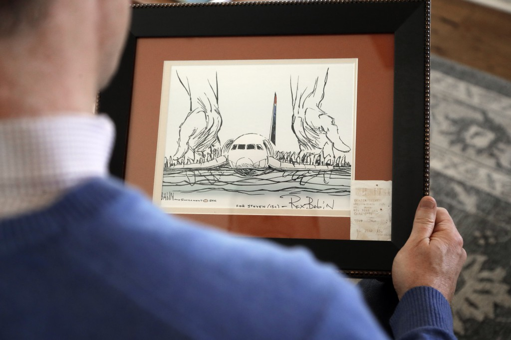 In this Jan. 10, 2019 photo, Steve O'Brien holds an editorial cartoon framed with his boarding pass from US Airways Flight 1549 that eventually crash-