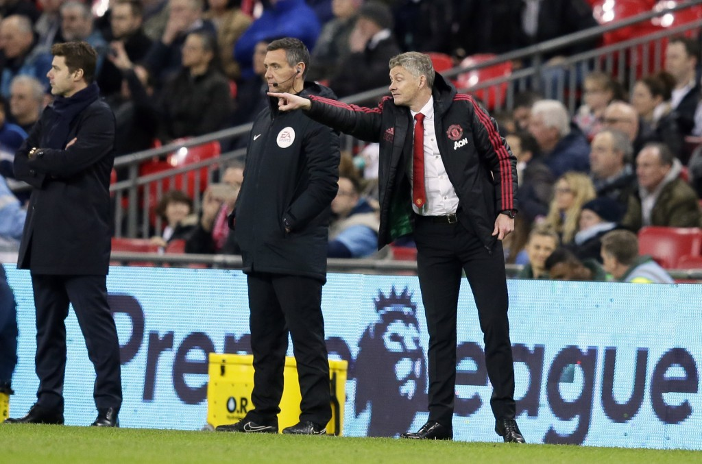 Manchester United caretaker manager Ole Gunnar Solskjaer gestures as Tottenham manager Mauricio Pochettino, left, looks on during the English Premier