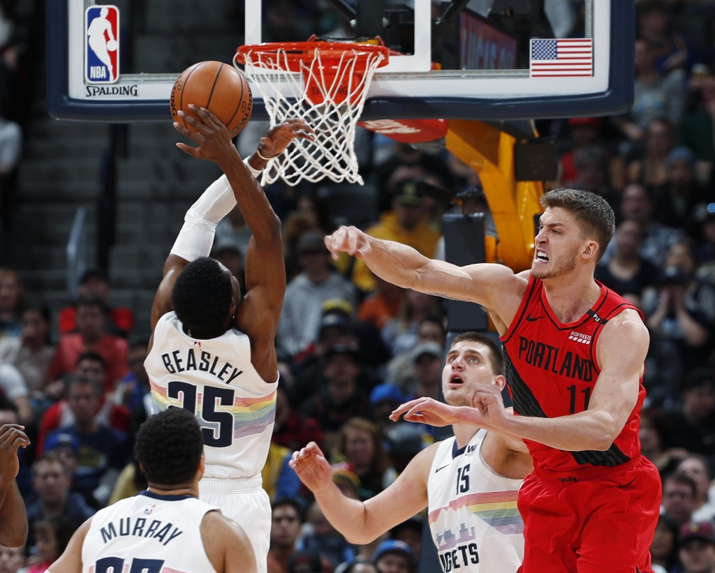 Portland Trail Blazers center Meyers Leonard, right, fights for control of a rebound with Denver Nuggets guard Malik Beasley in the first half of an N