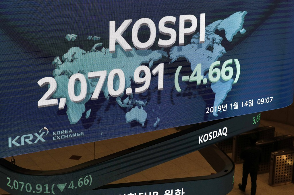 A man walks near the screen showing the Korea Composite Stock Price Index (KOSPI) at the Korea Exchange in Seoul, South Korea, Monday, Jan. 14, 2019.