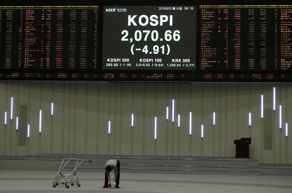 A worker checks the floor near the screen showing the Korea Composite Stock Price Index (KOSPI) at the Korea Exchange in Seoul, South Korea, Monday, J