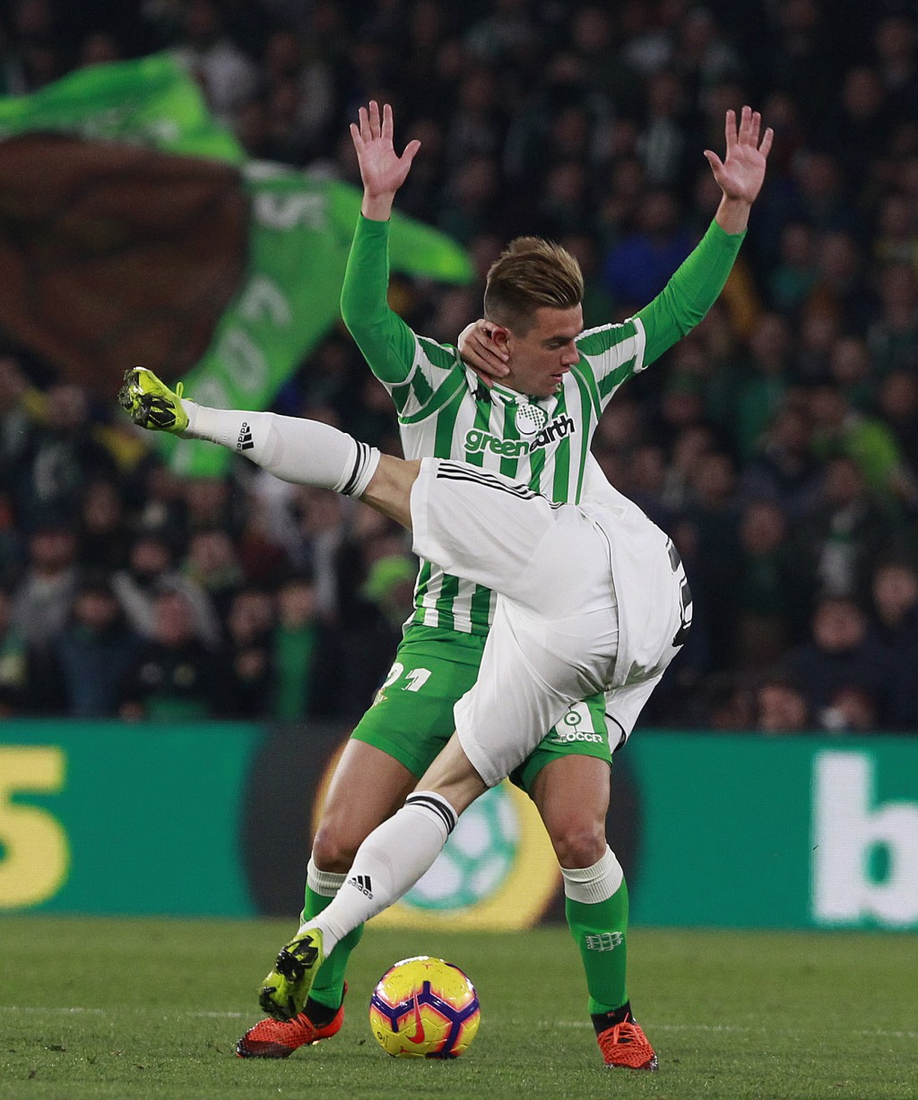 Real Madrid's Modric, front, and Betis' Lo Celso battle for the ball during La Liga soccer match between Betis and Real Madrid at the Villamarin stadi