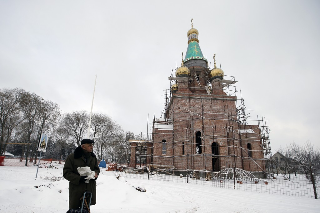 In this photo taken Friday, Jan. 11, 2019, a man walks by the new church under construction designed in the Russian style in the village Banstol in no...