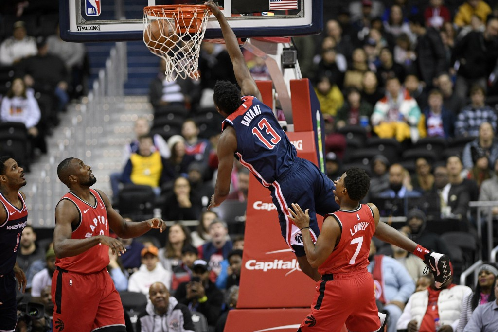 Washington Wizards center Thomas Bryant (13) dunks against Toronto Raptors guard Kyle Lowry (7) and forward Serge Ibaka (9) during the first half of a