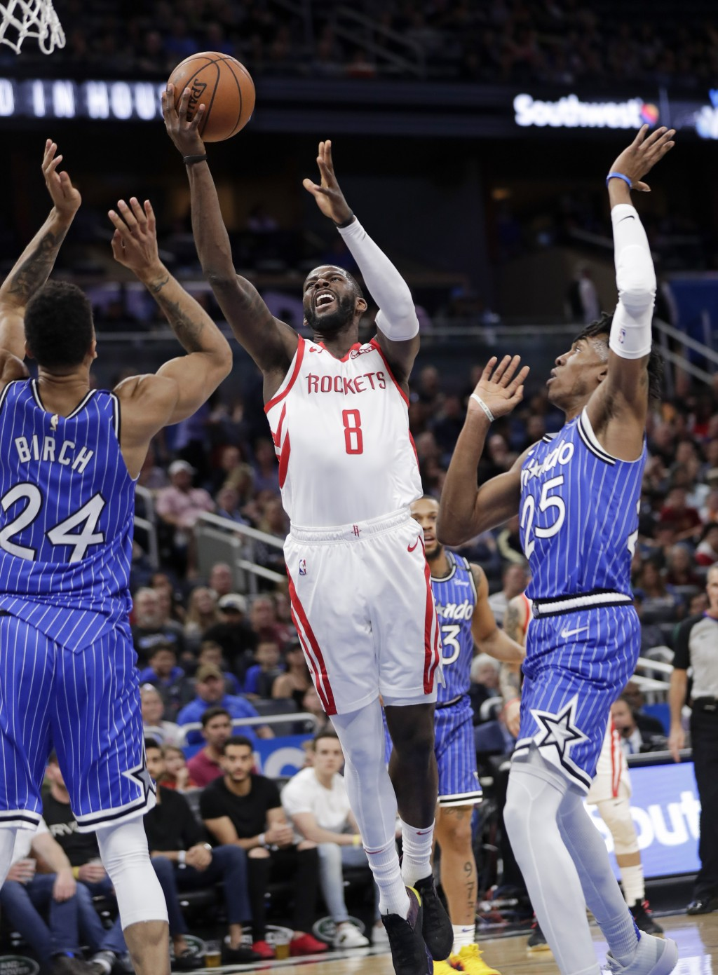Houston Rockets' James Ennis III (8) goes to the basket between Orlando Magic's Khem Birch (24) and Wes Iwundu (25) during the first half of an NBA ba