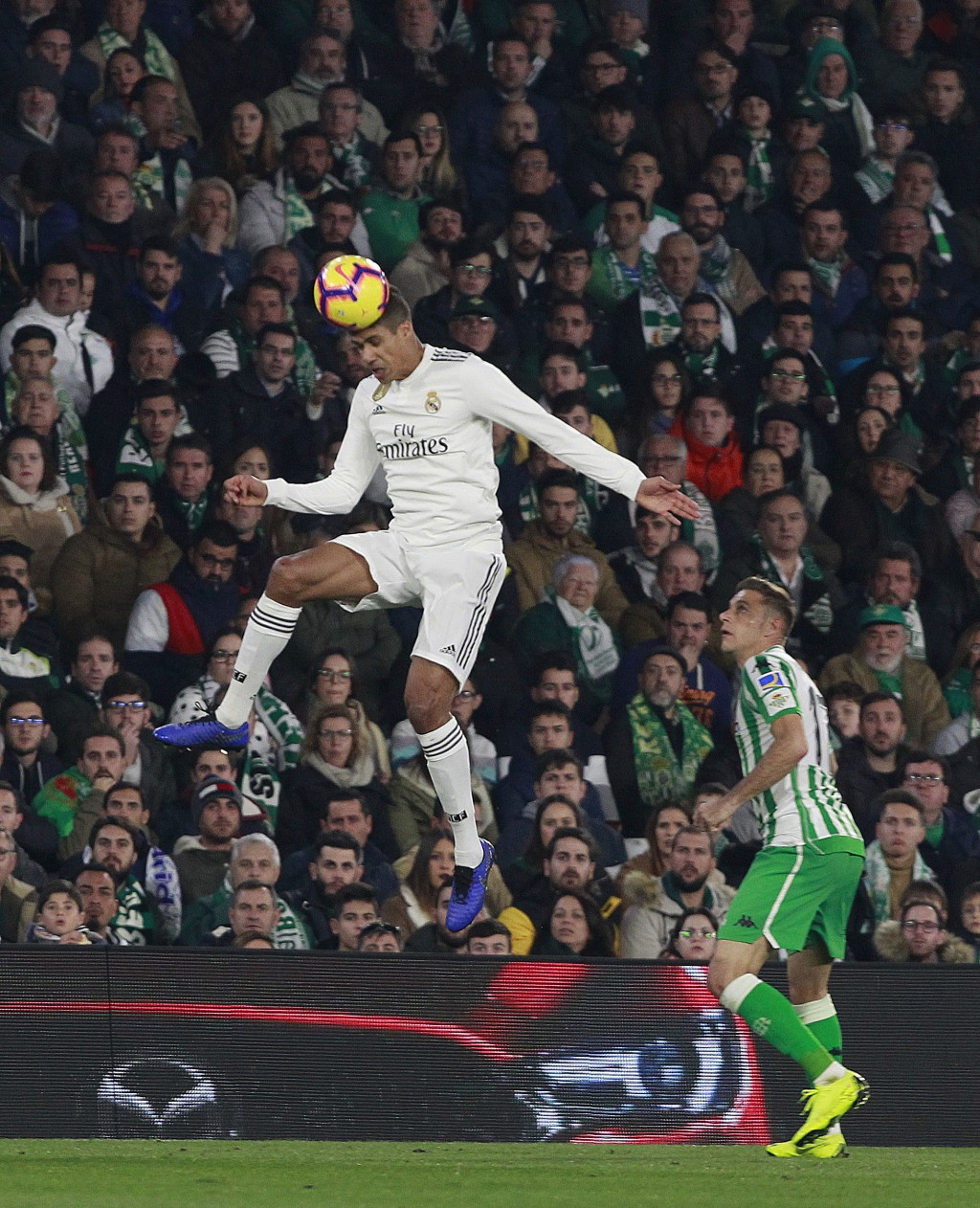 Real Madrid's Varane, left, jumps for the ball as Betis' Joaquin Sanchez looks on during La Liga soccer match at the Villamarin stadium in Seville, Sp