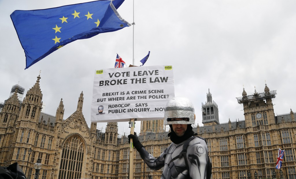 A protestor dressed as a robot demonstrates opposite the Houses of Parliament as Pro-European demonstrators protest in London, Monday, Jan. 14, 2019.