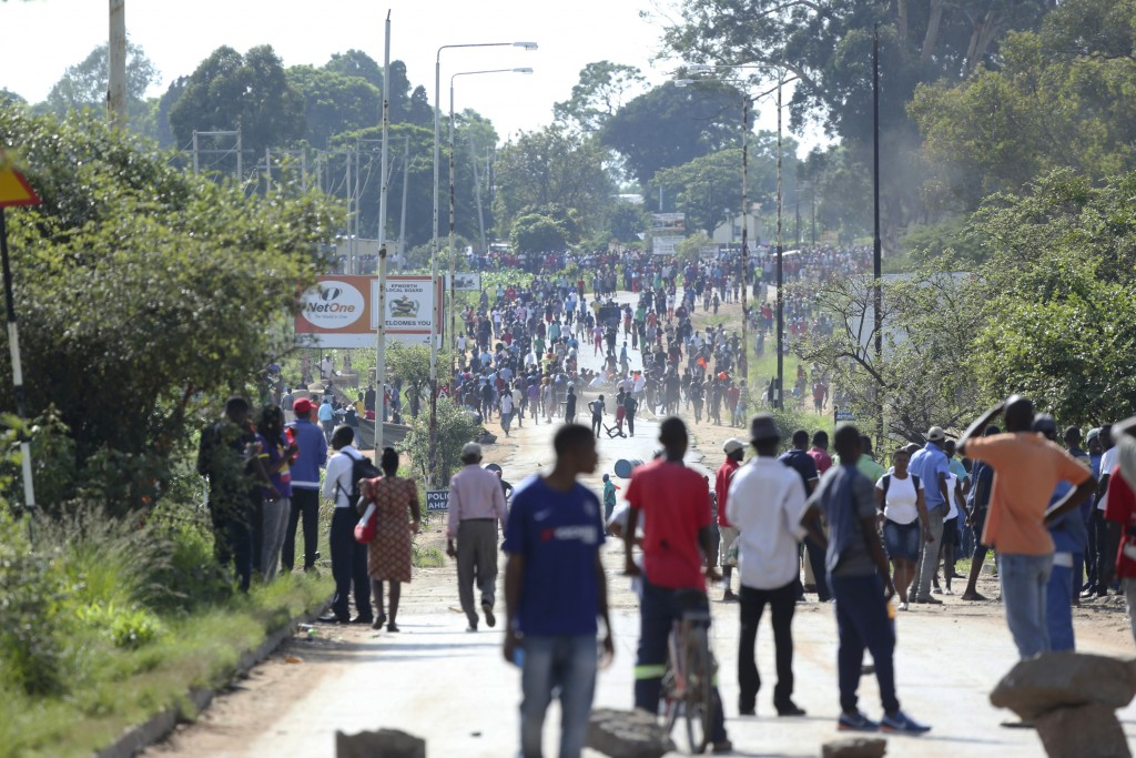 Protesters gather on a street during a demonstration over the hike in fuel prices in Harare, Zimbabwe, Monday, Jan. 14, 2019. Zimbabwean President Emm