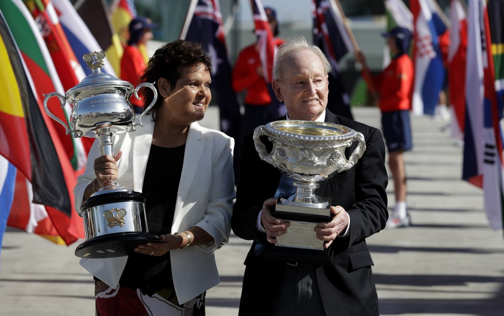 Australian tennis legends Evonne Goolagong Cawley and Rod Laver hold the women's and men's trophies, the Daphne Akhurst Memorial Cup and the Norman Br