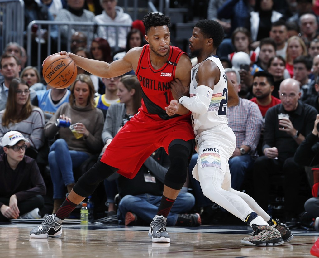 Portland Trail Blazers guard Evan Turner, left, works the ball inside as Denver Nuggets guard Malik Beasley defends in the first half of an NBA basket