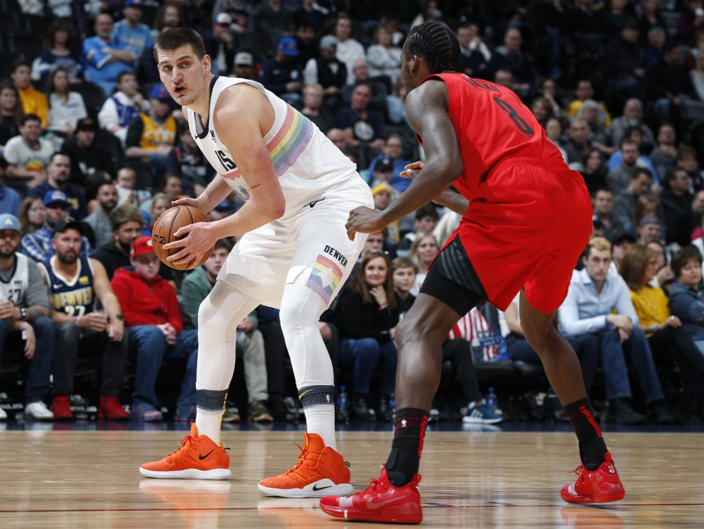 Denver Nuggets center Nikola Jokic, left, looks to pass the ball as Portland Trail Blazers forward Al-Farouq Aminu defends in the first half of an NBA