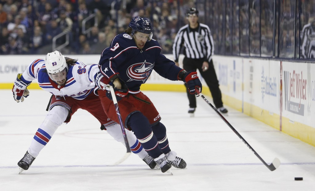 Columbus Blue Jackets' Artemi Panarin, right, of Russia, carries the puck across the blue line as New York Rangers' Mika Zibanejad, of Sweden, pursues
