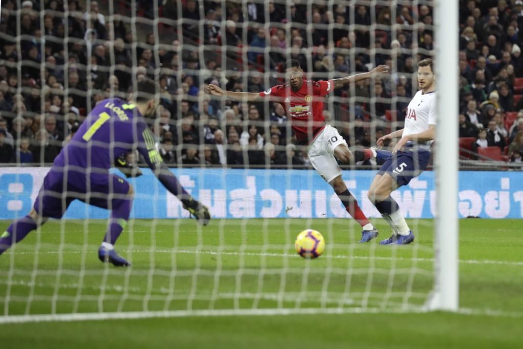 Manchester United's Marcus Rashford, center, scores his side's first goal passing Tottenham goalkeeper Hugo Lloris, left, and Tottenham's Jan Vertongh