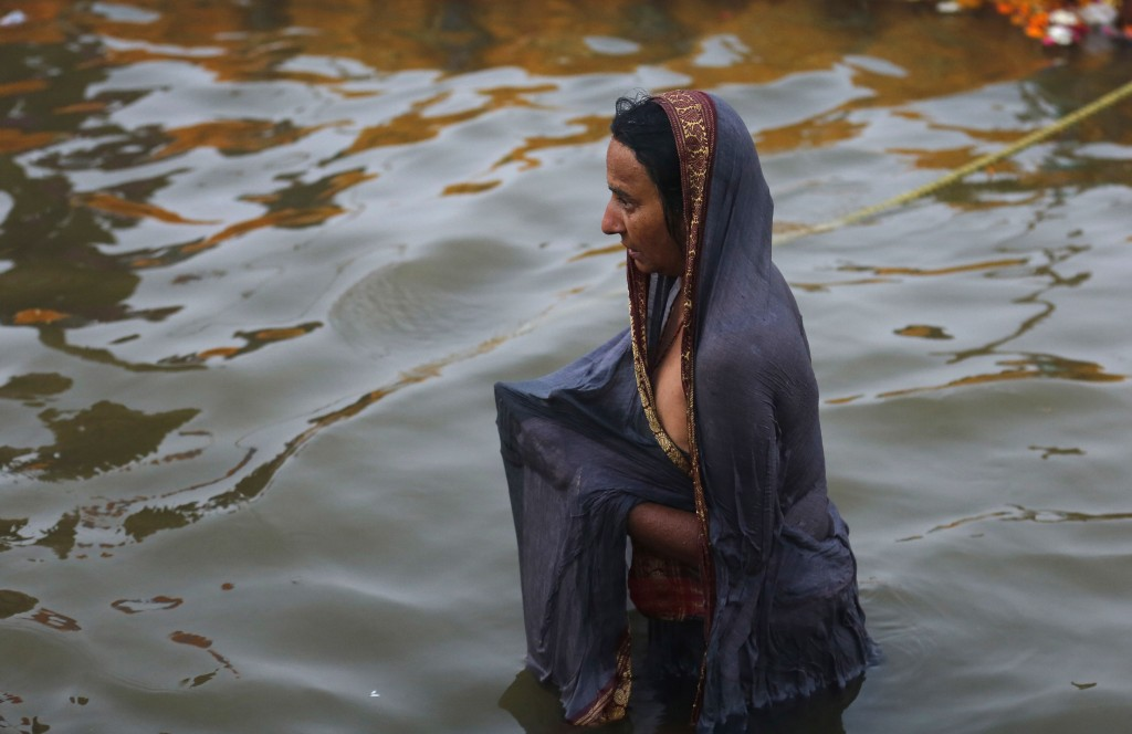 A Hindu devotee takes a spiritual-cleansing dip at the Sangam, the confluence of the Ganges, Yamuna, and the mythical Saraswati river during the Kumbh