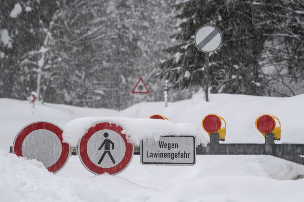 Due to the danger of an avalange a road is closed in Rottach-Egern, Germany, Sunday, Jan. 13, 2018. (Lino Mirgeler/dpa via AP)