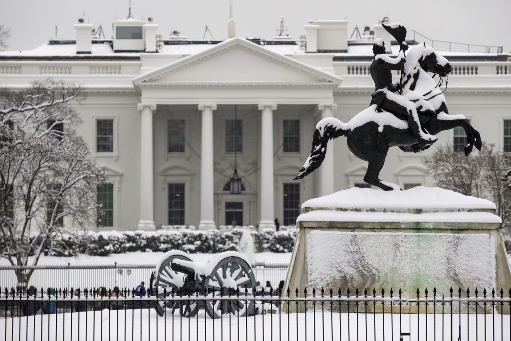 Snow blankets a statue of Andrew Jackson in Lafayette Square with the White House behind, as a winter storm arrives in the region, Sunday, Jan. 13, 20