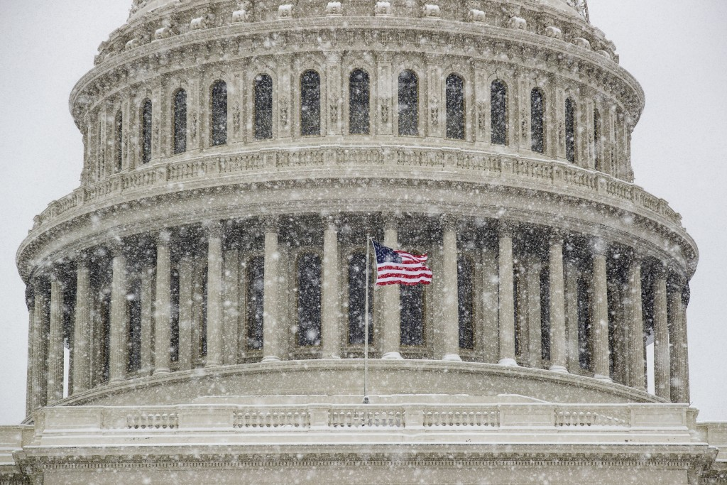 An American flag waves in front of the U.S. Capitol Dome as a winter storm arrives in the region Sunday, Jan. 13, 2019, in Washington. (AP Photo/Alex