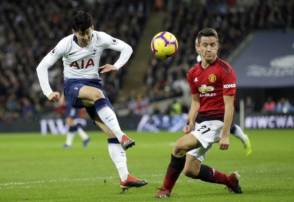 Tottenham's Son Heung-Min has a shot blocked by Manchester United's Ander Herrera, right, during the English Premier League soccer match between Totte