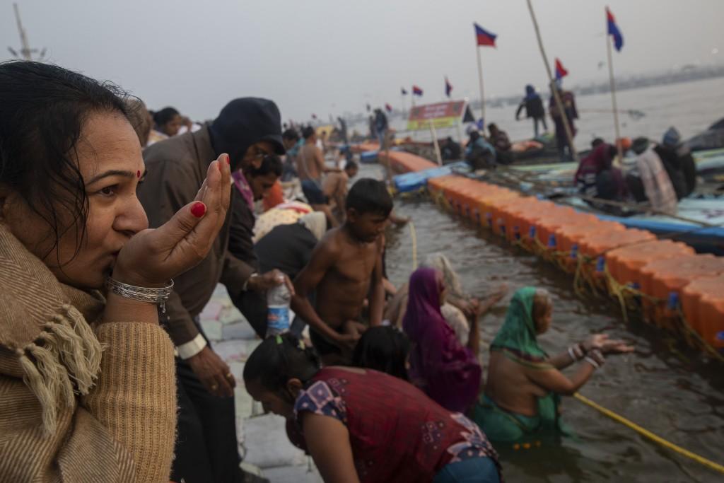 An Indian Hindu pilgrim prays at Sangam, the confluence of the rivers Ganges, Yamuna and mythical Saraswati, during the Kumbh Mela festival in Allahab