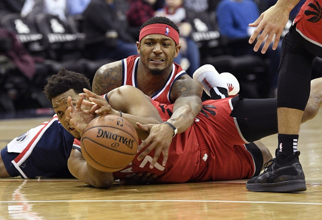Washington Wizards guard Bradley Beal, top, battles for the ball against Toronto Raptors guard Kyle Lowry during the second half of an NBA basketball