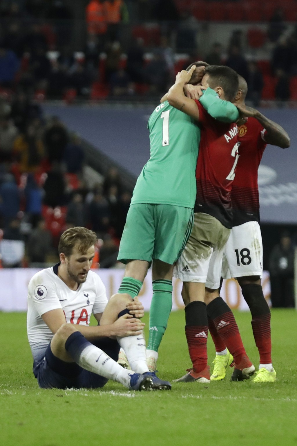 Tottenham's Harry Kane sits on the pitch with an injury as Manchester United players hugs teammate and goalkeeper David de Gea, left in green, after t