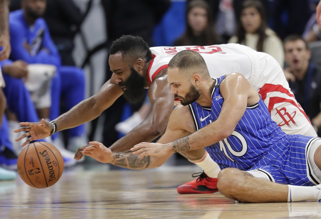 Houston Rockets' James Harden, left, and Orlando Magic's Evan Fournier (10) go after the ball during the second half of an NBA basketball game, Sunday